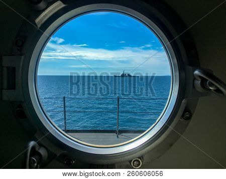 Window Port Of Navy Ship With Dogs For Locking The Window. Outside The Window Also Has Destroyer Sai