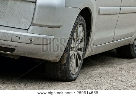 Part Of A Gray Car With A Bumper And A Dirty Wheel On The Road