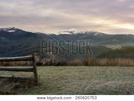 Wooden Fence On Meadow With Frozen Grass. Mysterious Late Autumn Scenery With Snow On Tops Of Distan