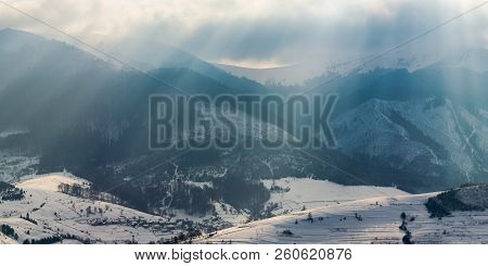 Gorgeous Panorama Of Mountains In Winter. Snowy Hills Lit With Sun Light Through Overcast Sky. Small