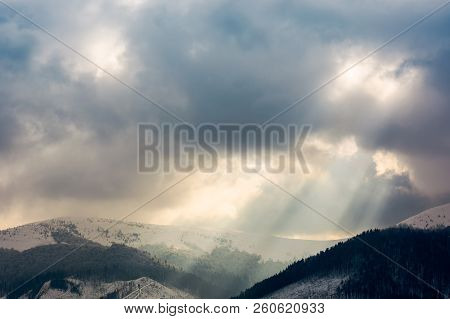 Overcast Sky With Light Beams Over The Ridge. Dramatic Winter Scenery In Mountains With Snowy Tops