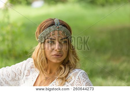 Head And Shoulders Portrait Of Beautiful Blonde Woman Wearing Boho Chic Vintage Headpiece And Thinki