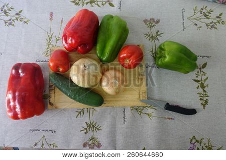 Onions, Green And Red Peppers And Cucumber All Raw And Whole On A Wooden Board On A Table With Old O