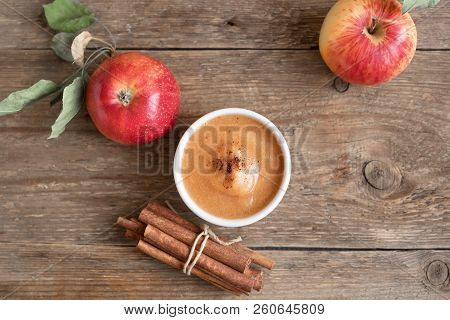Fresh homemade applesauce (apple puree, mousse, sauce) with cinnamon and apples on wooden table close up poster
