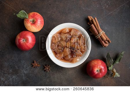 Homemade apple jam (apple chutney, marmalade, chunky sauce) with cinnamon, anise and apples on rustic background, top view. Traditional autumn apple jam. poster