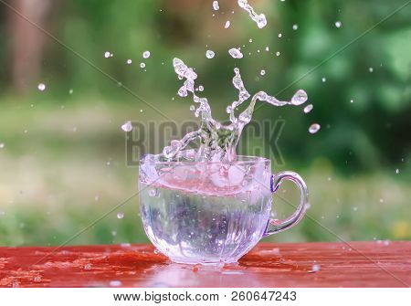 Splash Of Cool Fresh Water With Ice Cube In The Transparent Glass Cup In The Table Outoors In Summer