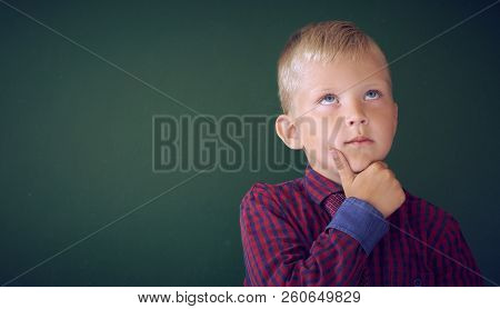 Closeup Shot Of Schoolboy Thinking With Hand On Chin Isolated On Blackboard. Portrait Of Pensive Chi