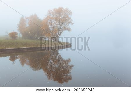 Foggy Autumn Gray Landscape With Red Orange Trees And Mirror Reflection In Lake, Horizontal Composit