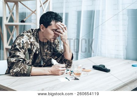 A Man In Camouflage At Home With Cigarette. Depression After War.. Depression After War Concept. Sad