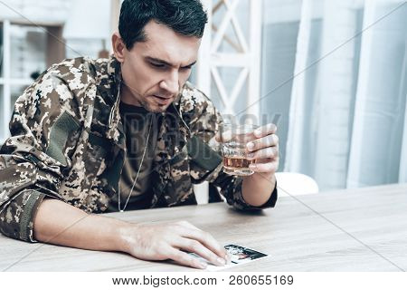 Man In Camouflage Drinking Alcohol. Depression After Military Actions Concept. Sad Homecoming. Retur