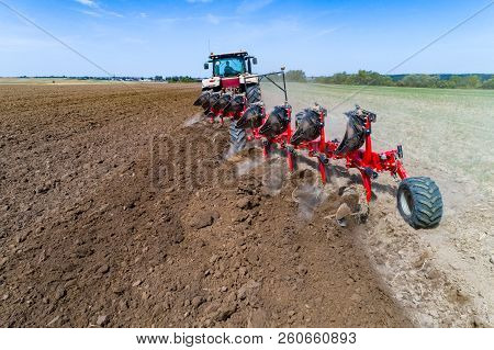 Close View On Element Of The Tractor Harrownig The Large Brown Field
