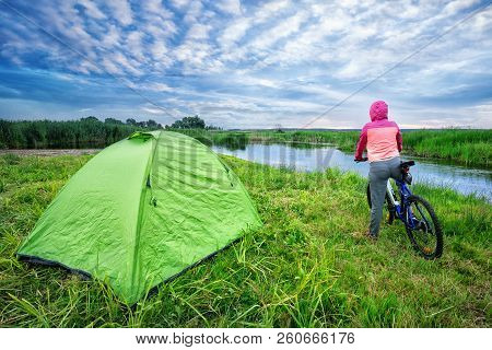 Girl With A Bicycle On The Lake Shore. A Girl Sits On A Bicycle Near A Tent On The Lake Shore. Summe