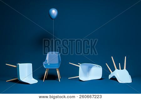 Blue Chairs Lying On Blue Room Floor. Dark Blue Chair With A Balloon Standing. Concept Of Being Uniq