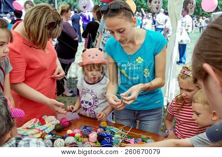 Zaporozhia/ukraine- June 2, 2018: Charity Family Festival-young Woman - Volunteer Explaining To Smal