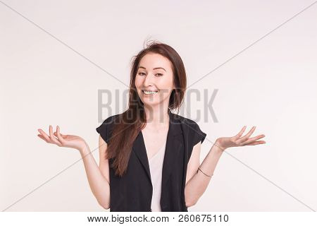 Young Brunette Asian Woman Is Shrugging Her Shoulders On White Background.