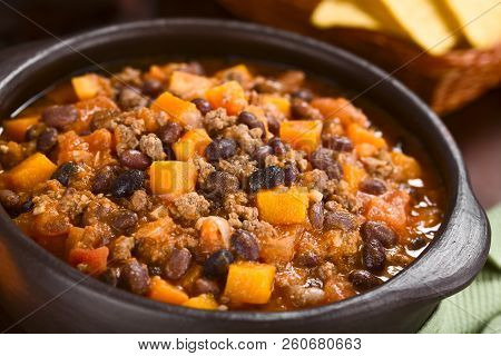 Homemade Chili Con Carne With Mincemeat, Red And Black Beans, Tomato Sauce And Pumpkin In Rustic Bow
