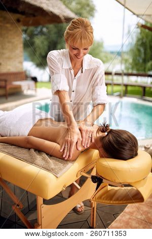 Beauty Spa Treatment-Smiling masseur is massaging a woman at home outdoor