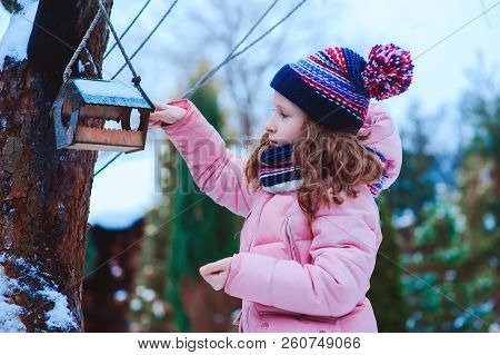 Child Girl Feeding Birds In Winter. Bird Feeder In Snowy Garden, Helping Birds During Cold Season, T