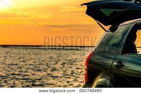 Black Compact Suv Car With Sport And Modern Design Parked On Concrete Road By The Sea At Sunset. Env