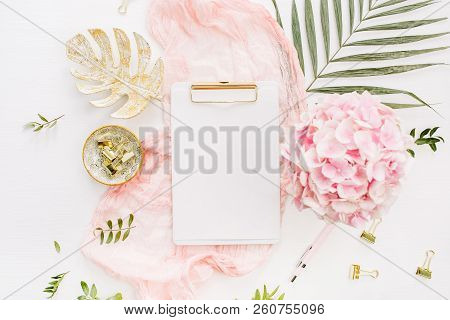 Modern Home Office Desk Workspace With Blank Paper Clipboard, Pink Hydrangea Flowers Bouquet, Tropic