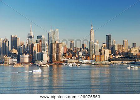 Manhattan, New York City skyline with empire state building over Hudson River.