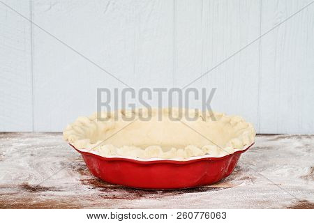 Homemade Butter Pie Crust In Pie Plate With Fluted Pinched Edge Against A Rustic Wooden Background.