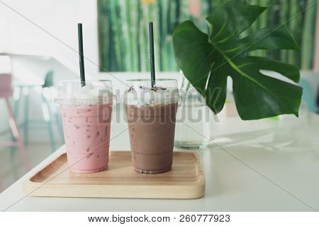 Two Plastic Take Away Cup Of Iced Black Coffee Americano And Iced Coffee Latte On Wood Table In Coff