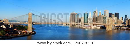 New York City Manhattan skyline panorama with Brooklyn Bridge and skyscrapers over Hudson River in the morning after sunrise.