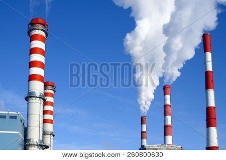 Chimneys Of Thermal Power Plant Against The Blue Sky. Modern Thermal Power Plant Against The Old The