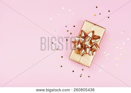Golden Gift Or Present Box And Stars Confetti On Pink Table Top View. Flat Lay Composition For Birth