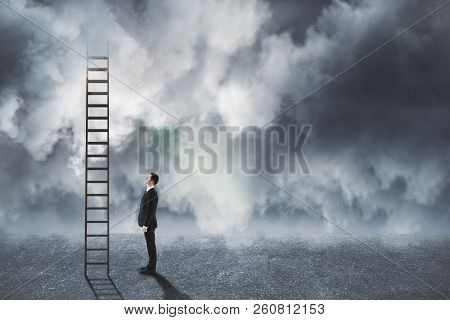 Young Businessman Looking At Ladder On Dull Cloudy Sky Background. Risk And Growth  Concept