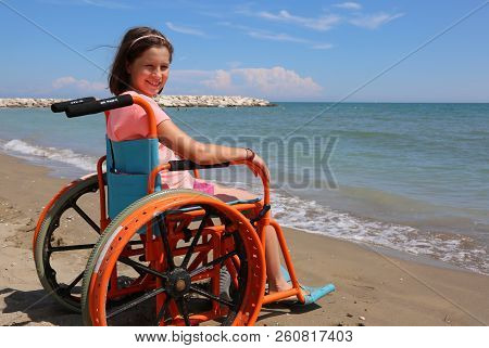 Little Girl On The Wheelchair With Special Wheels On The Beach