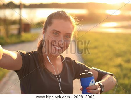 Young Attractive Woman In Sports Clothing Looking At Phone And Smiling While Taking Selfie, During O