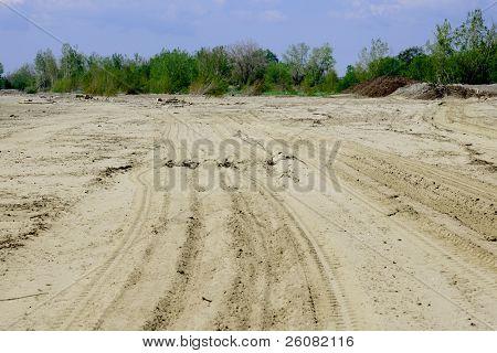 Tire tracks mark the sand on a beach.