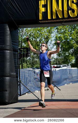 Triathlete crosses the finish line.