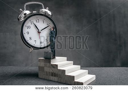 Businessman Stands On Stairs And Tries To Change Clock Hand Position. Surrealistic Conception Of Tim