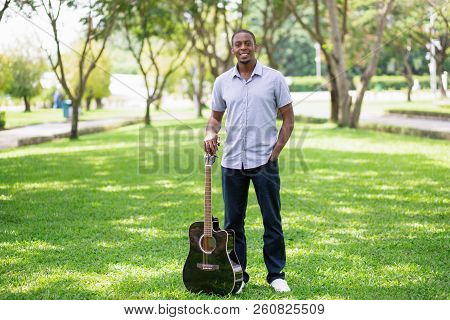 Smiling Young Guy Holding Guitar By Headstock In Park. Handsome Black Man Standing And Looking At Ca