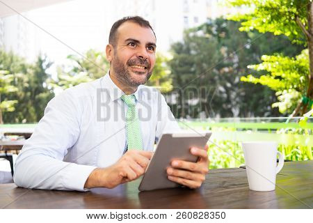 Portrait Of Smiling Mature Businessman Using Digital Tablet At Cafe. Caucasian Manager Networking On