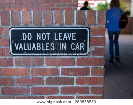 People Walking Away From Do Not Leave Valuables In Car Sign