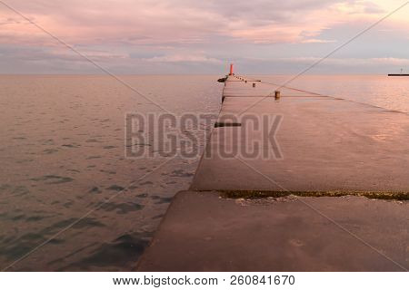 A Lighthouse Pier On Lake Michigan At Sunset With Pink Clouds Reflected In The Water.  Sheboygan, Wi