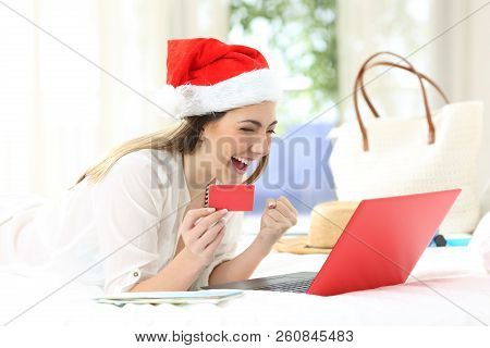 Excited Woman Buying Online On Christmas Holidays Lying On A Bed In An Hotel Room