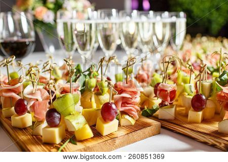 The Buffet At The Reception. Glasses Of Wine And Champagne. Assortment Of Canapes On Wooden Board. B