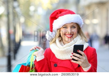 Front View Portrait Of A Happy Shopper Shopping Online Looking At Camera On Christmas Holidays On Th