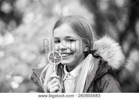 Little girl eat candy on stick, food. Child smile with lollipop, snack. Food, snack, dessert for small child on nature. Happy childhood and youth. Kid beauty, fashion, look poster
