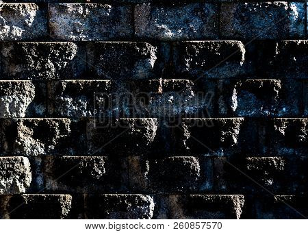 Aged Worn Grungy Cement Block Wall With Dirt And Moss Showing Angled Light