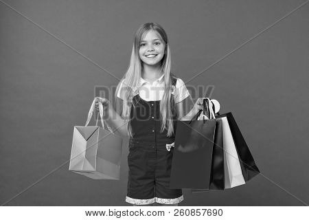 Girl On Smiling Face Carries Bunches Of Shopping Bags, Isolated On White Background. Girl Likes To B