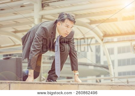 Attractive Business Man With A Suitcase In Start Position Runner City Background Ready For The Start