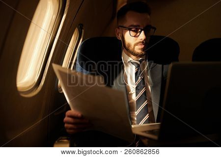 Portrait Of Successful Young Businessman Working In Dim Plane While Enjoying First Class Flight, Cop