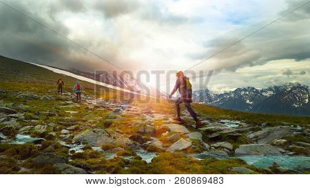 Group Of Running On A Mountain Trail. Backpacks For Running Behind His Backs And Poles In Hand. Rays