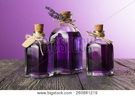 Three Glass Jars With Aromatic Tincture Of Lavender On Dark Wooden Boards